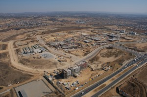 An aerial photograph showing the construction boom at Waterfall, Attacq's trail-blazing mixed-use property development centrally situated between Pretoria and Sandton. Construction on the R4.1 billion Mall of Africa is in the centre of the photograph, while the new City Lodge hotel is in the foreground.