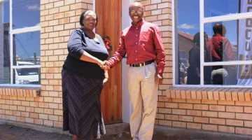 A delighted Annie Motlhodiemang with Musa Shangase, Corobrik's Commercial Director outside her new home built from Corobrik Nebraska Travertine Light face brick.