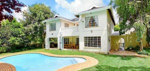 A poolside view of a four bedroom, two bathroom home on the market for R2, 850, 000.