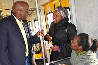 Executive Mayor, Clr Mondli Gungubele solicits views about public transport from train commuters.